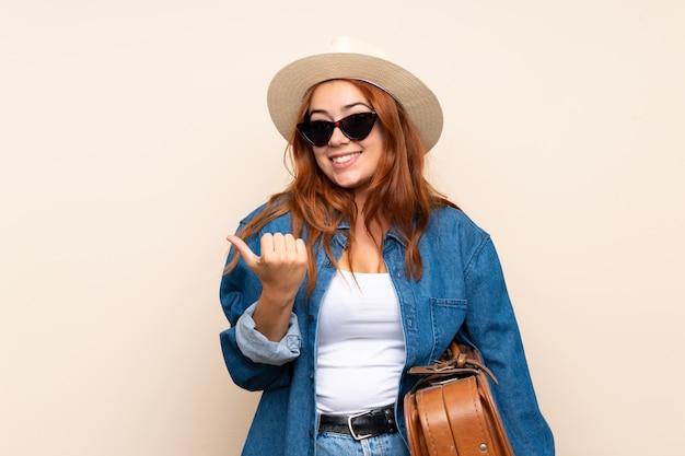 製品を提示する側を指しているスーツケースと赤毛の旅行者の女の子