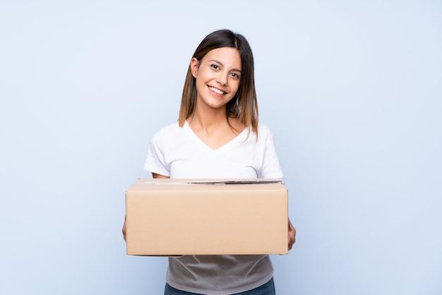 Молодая женщина над изолированным синим держит коробку, чтобы переместить ее на другой сайт