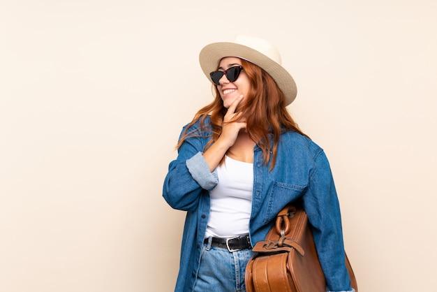 アイデアを考えて、側を見てスーツケースで赤毛の旅行者の女の子