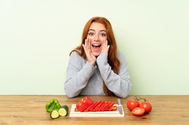 Рыжая девушка подросток с овощами в столе, крича с широко открытым ртом