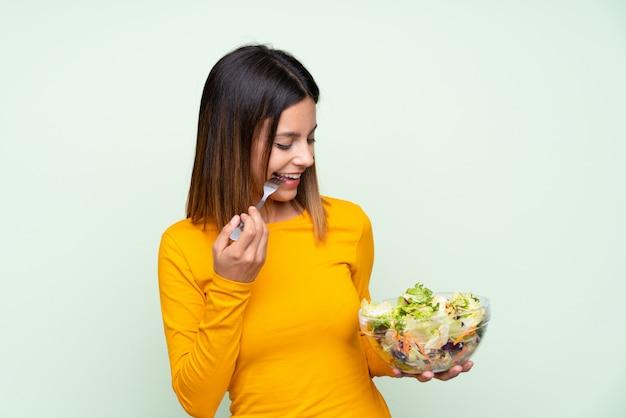 孤立した緑の壁の上のサラダを持つ若い女性