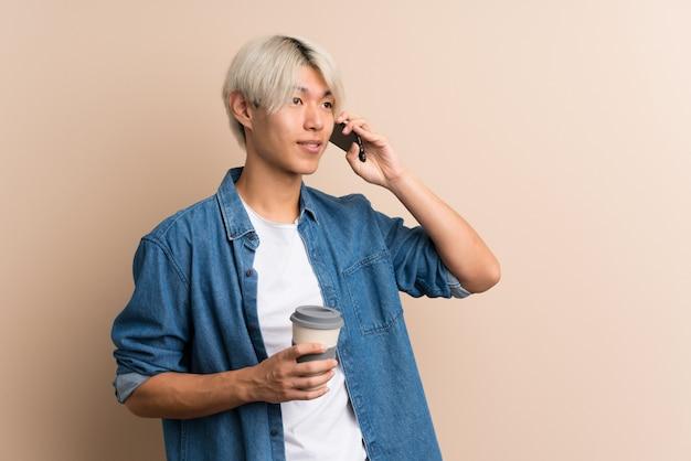 持ち帰るコーヒーと携帯電話を保持している若いアジア人