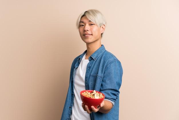 Молодой азиатский человек держа миску хлопьев