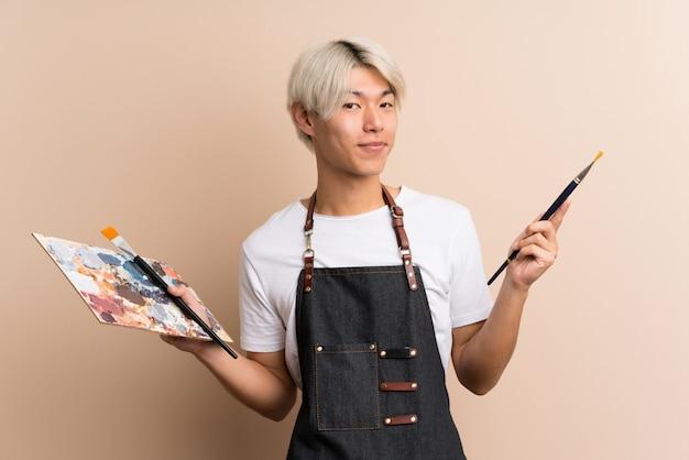 Молодой азиатский человек держа палитру