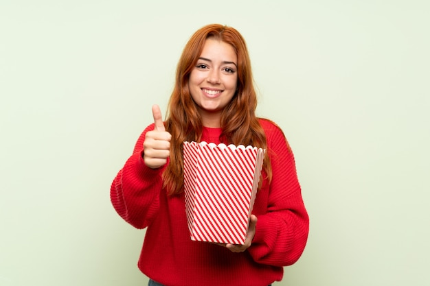 Рыжая девушка подросток с свитер над зеленым, держа миску попкорна