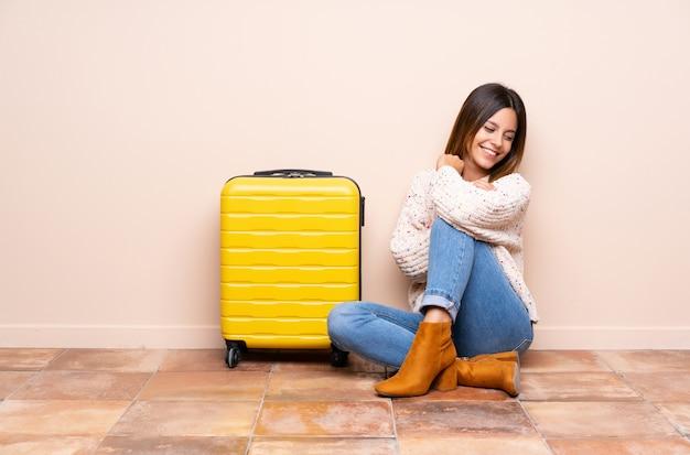 Путешественник женщина с чемоданом, сидя на полу от смеха