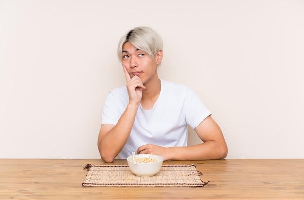 アイデアを考えてテーブルにラーメンを持つ若いアジア人