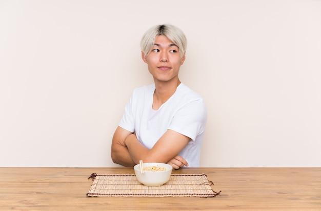 Молодой азиатский человек с рамэном в таблице смеясь над