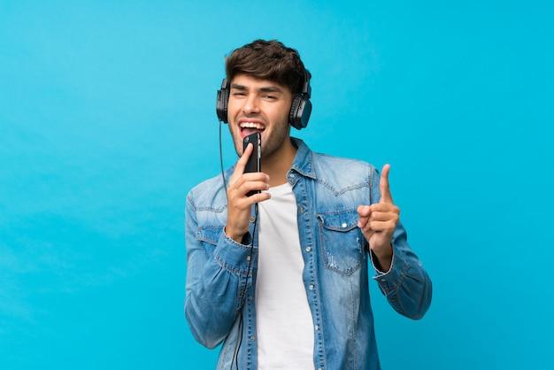 ヘッドフォンと歌で携帯電話を使用して分離された青の上の若いハンサムな男