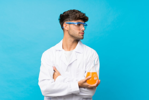 科学的なテストチューブと横向きに分離された青の上の若いハンサムな男