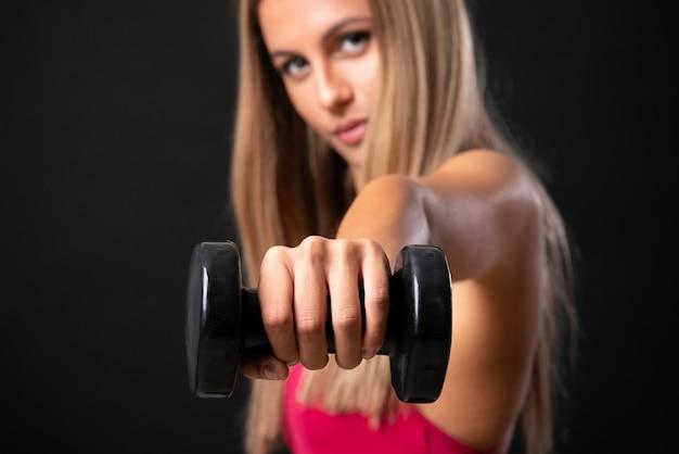 孤立した黒の上重量挙げを作る若いスポーツブロンドの女性