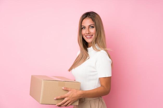Молодая белокурая женщина над изолированным пинком держит коробку для того чтобы переместить ее на другое место