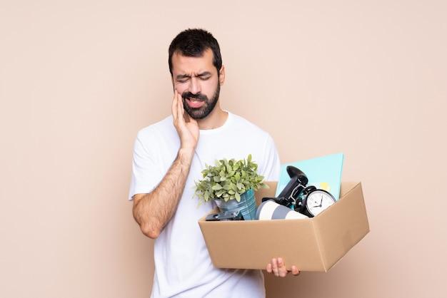 箱を抱えて歯痛で新しい家に移動する男