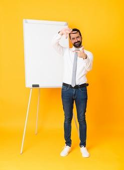 孤立した黄色のフォーカシング顔にホワイトボードでプレゼンテーションを行う実業家の全身ショット。フレーミングシンボル