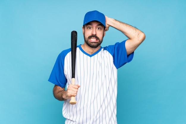孤立した青い壁に野球をしている若い男がイライラし、頭に手を取ります