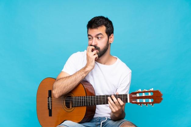 疑問を持つ分離の青い壁の上のギターを持つ若い男