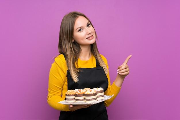 側に指を指している分離の紫色の壁にさまざまなミニケーキの多くを保持しているティーンエイジャーの女の子