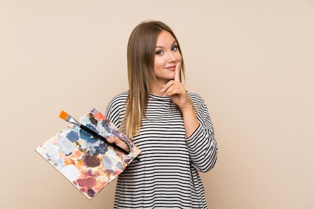 Девушка подростка держа палитру над изолированной стеной делая жест безмолвия