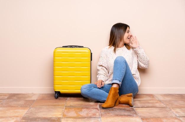 Путешественник женщина с чемоданом, сидя на полу, крича с широко открытым ртом