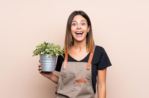 驚きとショックを受けた表情で植物を保持している若い女性
