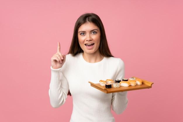 素晴らしいアイデアを指している分離のピンクの背景の上の寿司を持つ少女