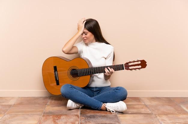混乱して表情を持つ疑いを持つ床に座ってギターを持つ若い女性