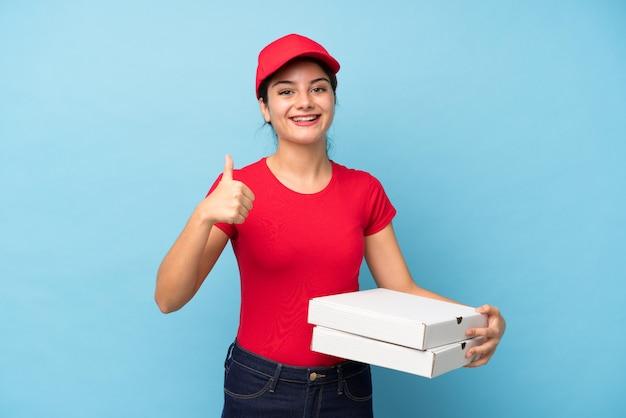 ジェスチャーを親指を与える分離のピンクの壁にピザを置く若い女性