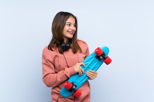 孤立した壁の上の若いスケーターの女の子