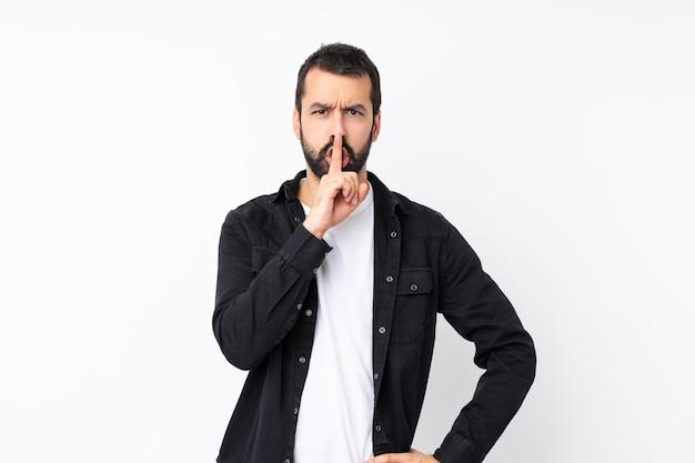 Молодой человек с бородой над изолированной белой стеной, показывая знак жеста молчания, положив палец в рот