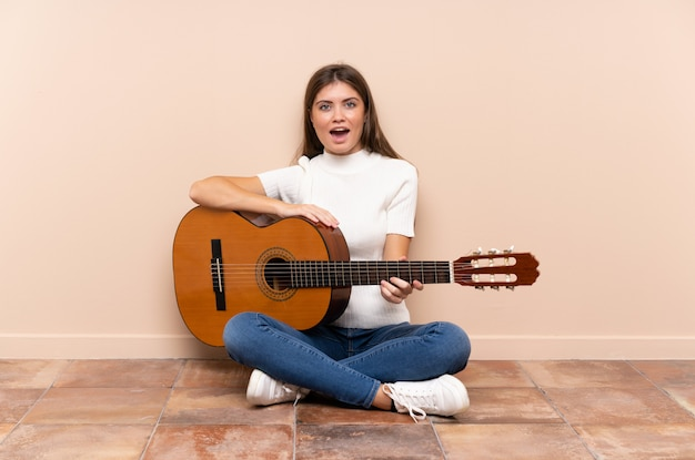 驚きの表情で床に座ってギターを持つ若い女性
