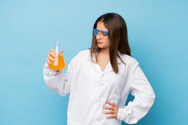 科学的なテストチューブを持つ若いブルネットの少女