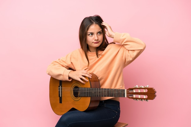 ギターの背景に疑問があると混乱の表情を持つ若いブルネットの少女