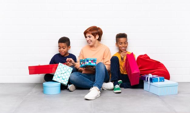 Афроамериканские дети со своей матерью среди множества подарков на рождественские праздники