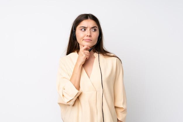 Молодая женщина телемаркетера над изолированной белой стеной думая идея
