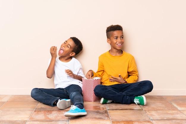 ポップコーンを持って幸せなアフリカ系アメリカ人の兄弟
