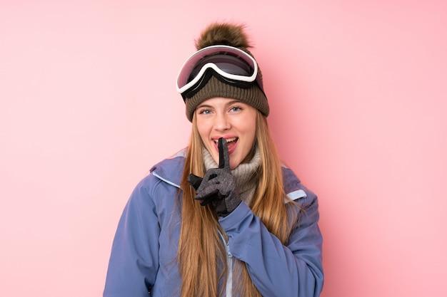 Девушка подростка лыжника с предпосылкой стекел сноубординга делая жест молчания
