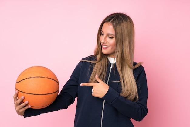 バスケットボールのボールとそれを指している若いブロンドの女性の背景