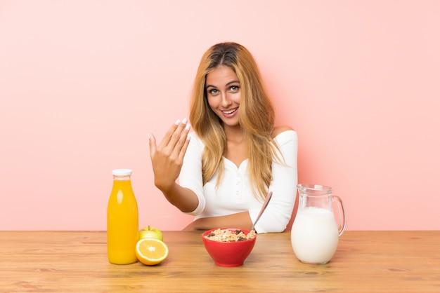 来るように誘う朝食牛乳を持つ若いブロンドの女性