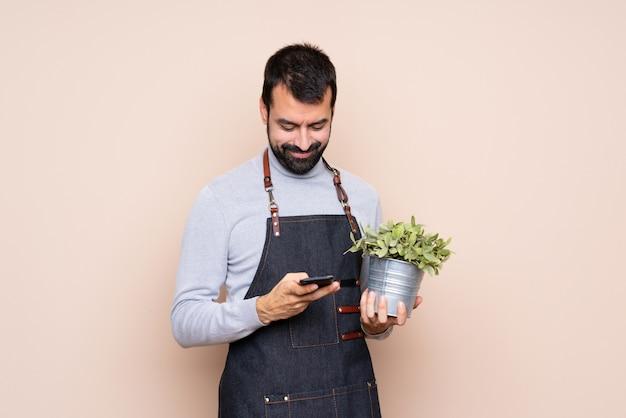 携帯電話でメッセージを送信する植物を抱きかかえた