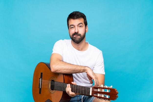 Молодой человек с гитарой над изолированной синей расстроен