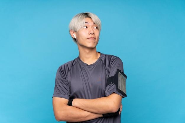 肩を持ち上げながらジェスチャーを作る分離青上の若いアジアスポーツ男