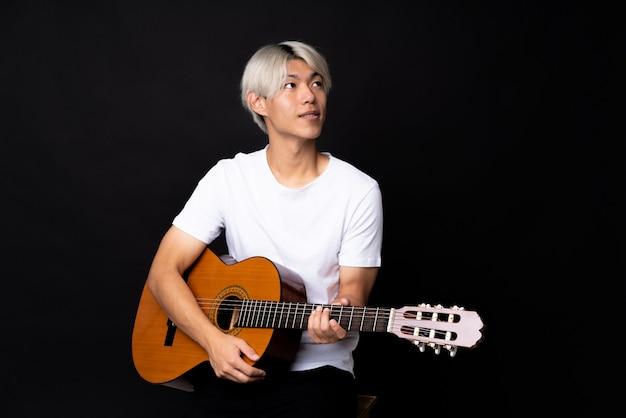 笑みを浮かべながら見上げる黒の上のギターを持つ若いアジア男