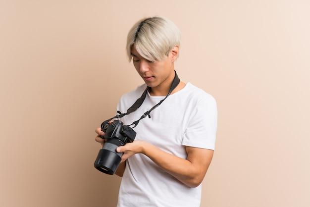 Молодой азиатский мужчина с профессиональной камерой