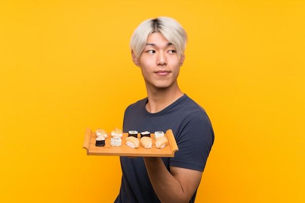 孤立した黄色の笑いで寿司を持つ若いアジア男
