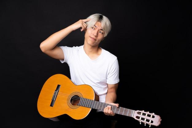 疑問を持つ黒と混乱の表情とギターを持つ若いアジア男