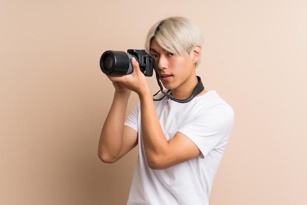 Молодой азиатский человек над изолированный с профессиональной камерой