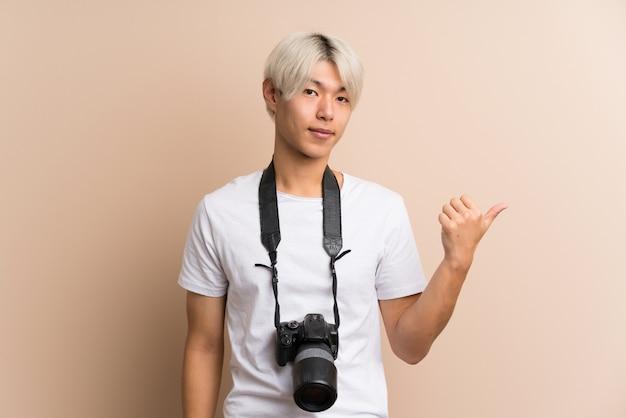Молодой азиатский человек над изолированный с профессиональной камерой и указывать к стороне