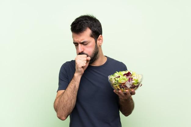 Молодой красавец с салатом на изолированной зеленой стене страдает от кашля и плохо себя чувствует
