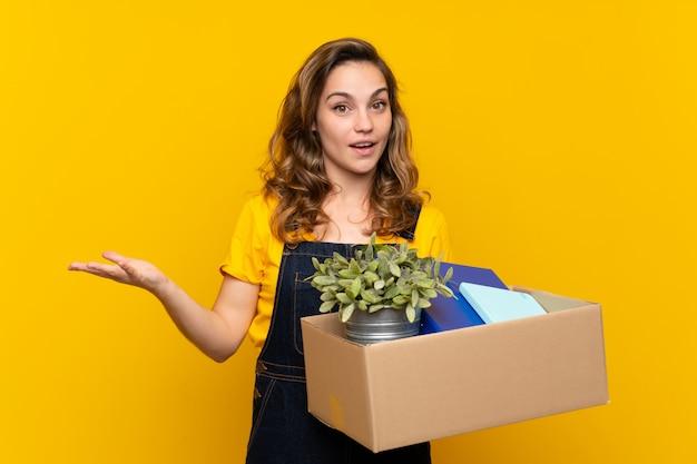 ショックを受けた表情で物事の完全なボックスを拾いながら移動を行う若いブロンドの女の子