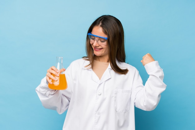 科学的な試験管とお祝いで分離された青の上の若いブルネットの少女